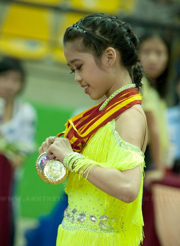 Cô bé đang say sưa với huy chương của mình