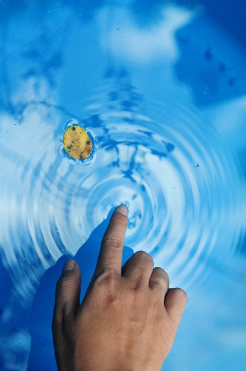 Tác phẩm đạt giải nhất chủ đề Chạm của Huỳnh Thái Sơn với hình ảnh ngón tay chạm vào mặt nước xanh.