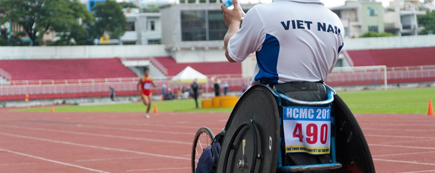 VĐV này bị tật ở chân, anh ngồi lên xe lăn để nhanh chóng di chuyển đến gần hơn để cổ vũ cho đồng đội.