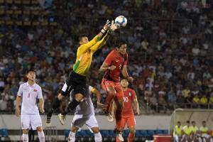 Thủ thành Tiến Dũng bắt bóng ngay trên đầu trung vệ đội khách