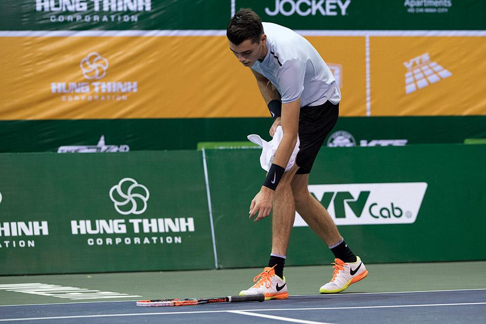 Fritz thất vọng ném vợt xuống sân