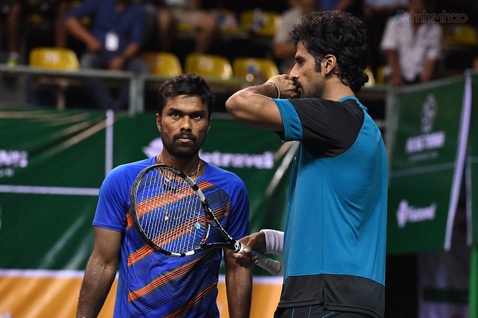 Tay vợt Ấn Độ che miệng bằng mu bàn tay trong khi bàn chiến thuật với đồng đội